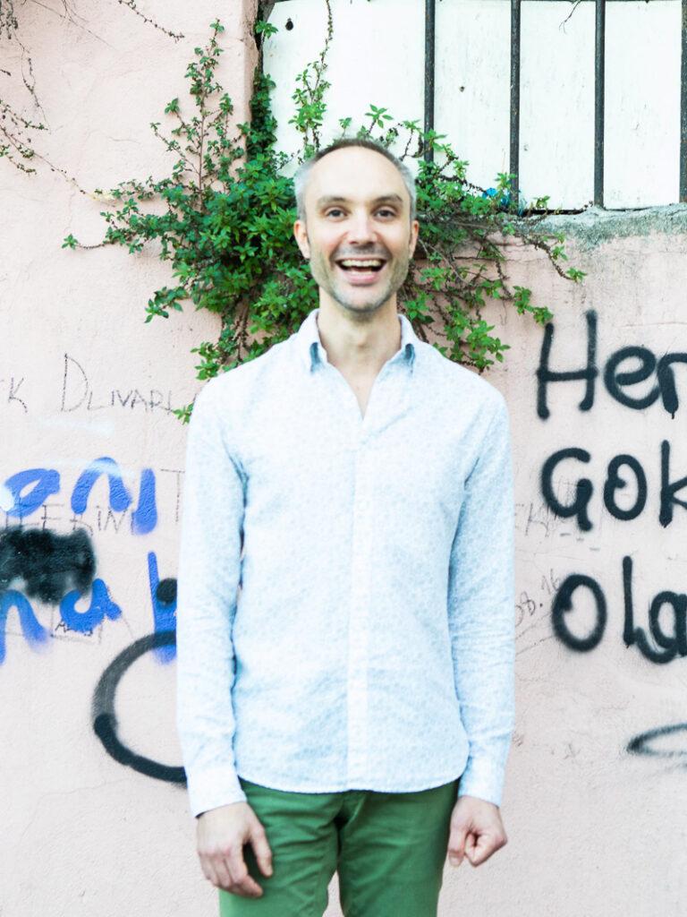 Vidar Bergum med stort smil foran en rustikk mur