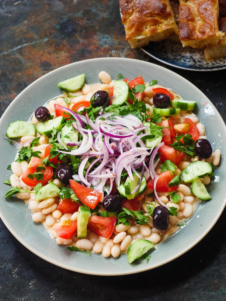 Antalya piyaz, en bønnesalat med tahinisaus toppet med frisk tomat, agurk, bladpersille, rødløk og svarte oliven