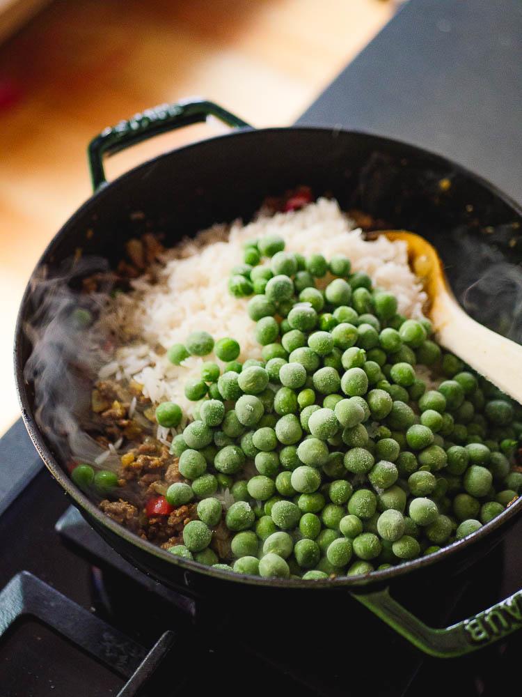 Stekt kjøttdeig med rå ris og frosne erter i varm stekepanne