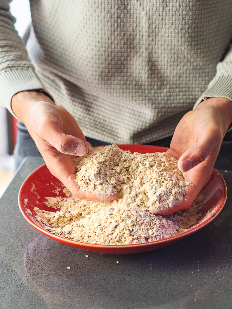 Hender blander havregryn og mel i rød bolle