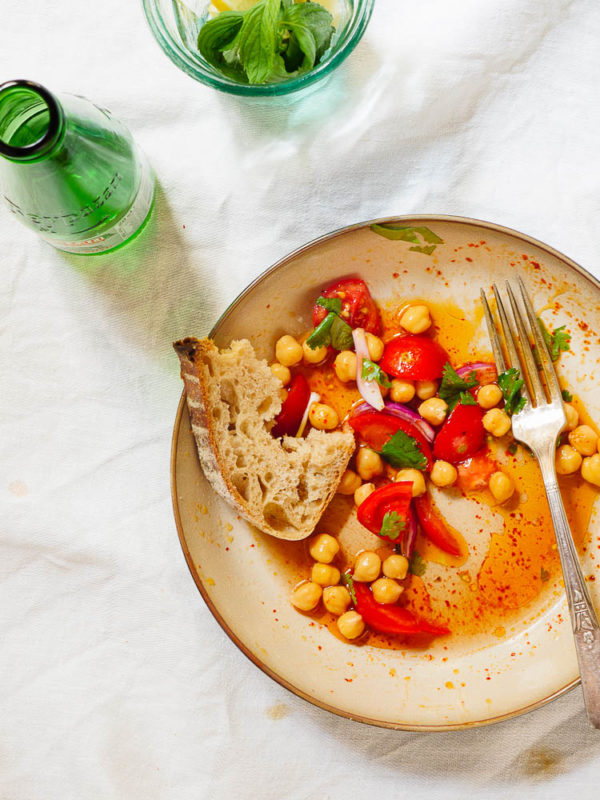 Delvis oppspist kikertsalat med tomat og koriander sett ovenfra