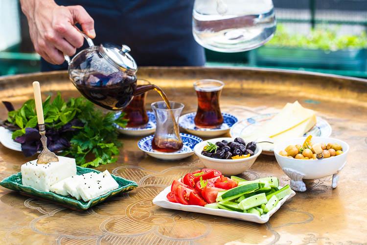 Tyrkisk frokost med te som helles i teglass i bakgrunnen
