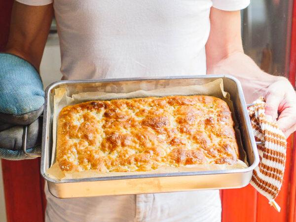 Ferdigstekt focaccia i hendene til kokken, sett fra siden