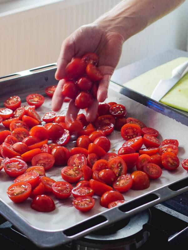 Helling av tomater på stekebrett kledd med bakepapir