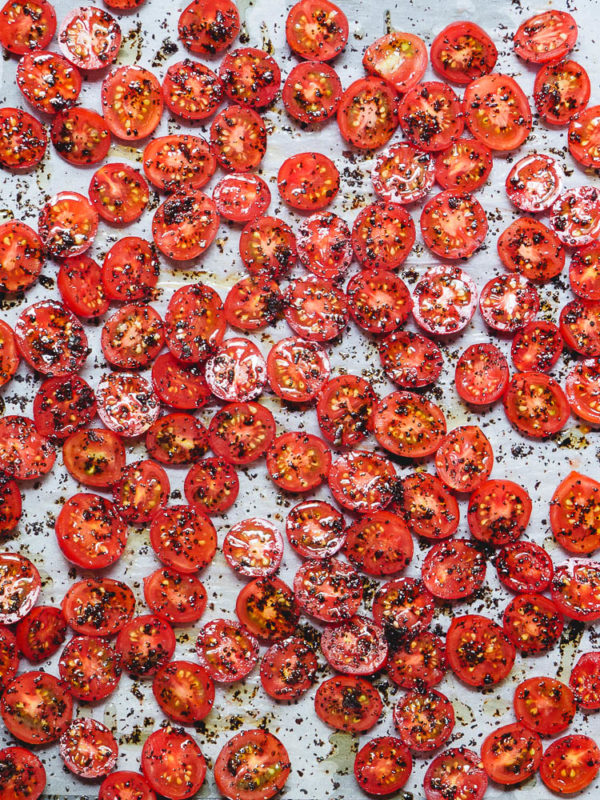 krydrede og oljede tomater på stekebrett klar for ovnen, sett fra oven