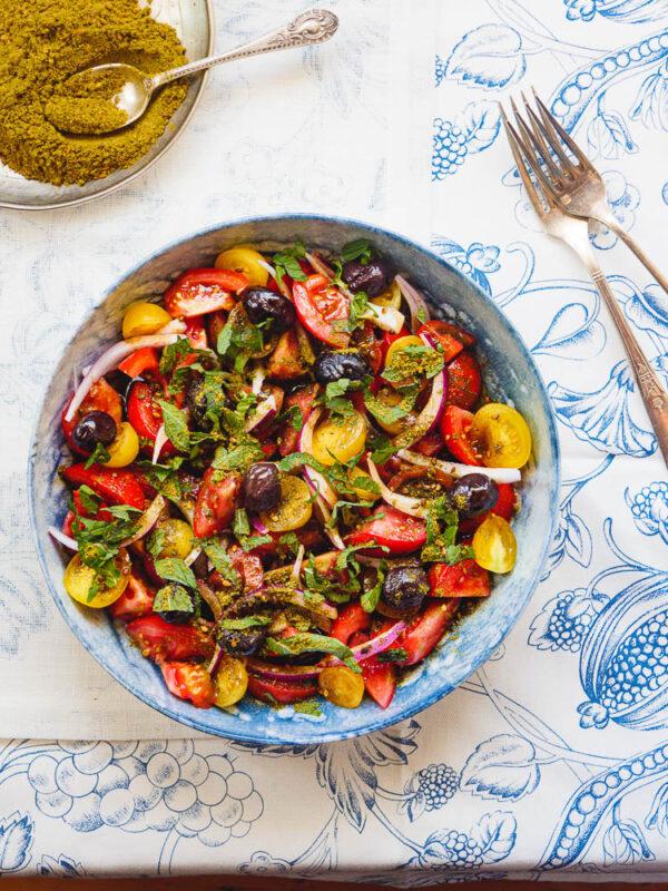 Tomatsalat med oliven og za'atar i blå bolle sett ovenfra