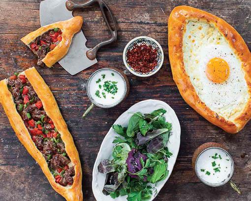 Tyrkisk og georgisk pizza på mørkt bord med salat i midten