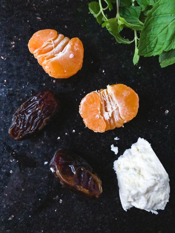 Klementiner, dadler, fetaost og mynte på mørk bakgrunn
