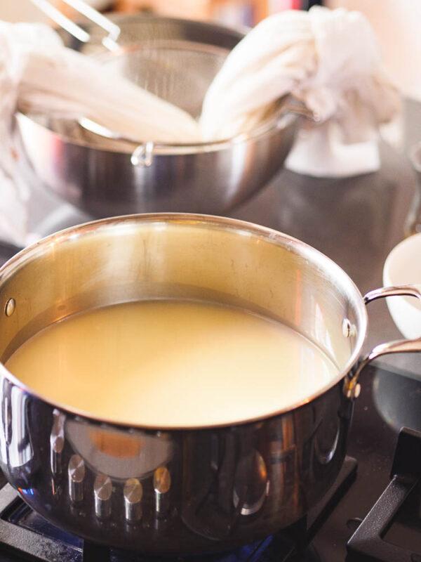 Myse i kasserolle klar for innkoking, med ostemasse i osteklede til avrenning i bakgrunnen