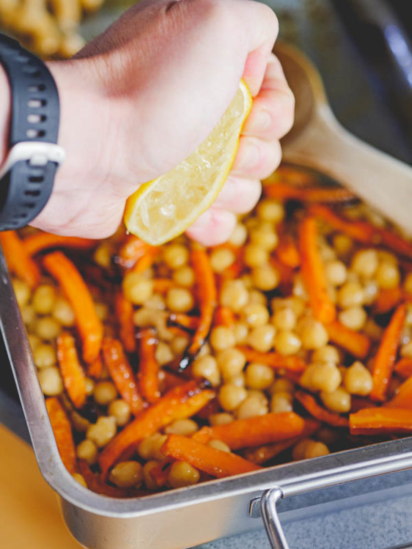 Hånd skviser sitron over lune kikerter med gulrot og karve