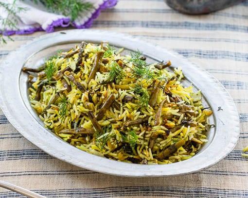 Iransk ris med grønne bønner og dill i tradisjonelt serveringsfat av metall, sett fra siden.