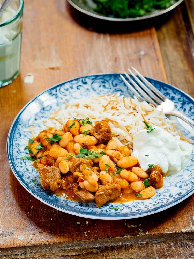 Tyrkisk bønnegryte med kjøtt, ris og yoghurt på tallerken med blått mønster, sett fra siden