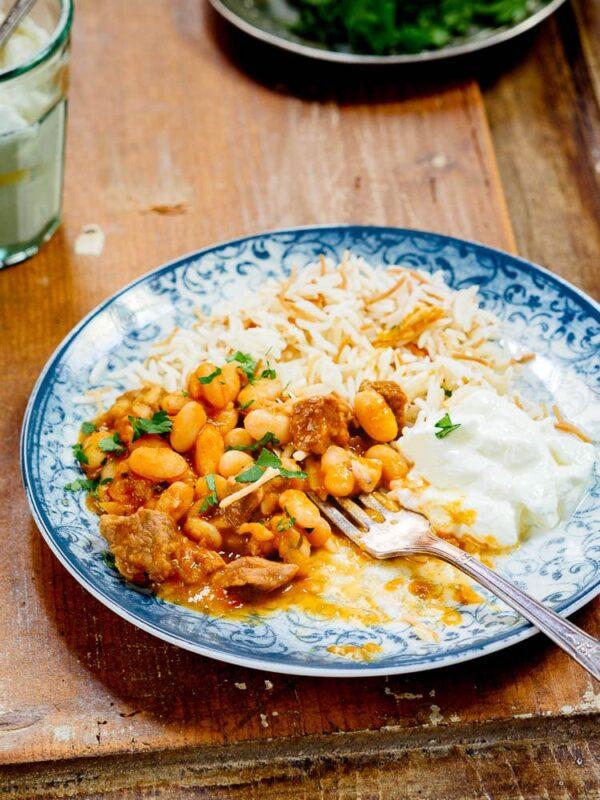 Halvspist tyrkisk bønnegryte med kjøtt, ris og yoghurt på tallerken med blått mønster, sett fra siden