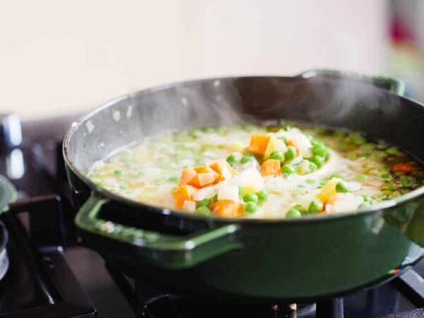 Artisjokk med erter og gulrot kokes i kasserolle, sett fra siden med røyk som kommer opp