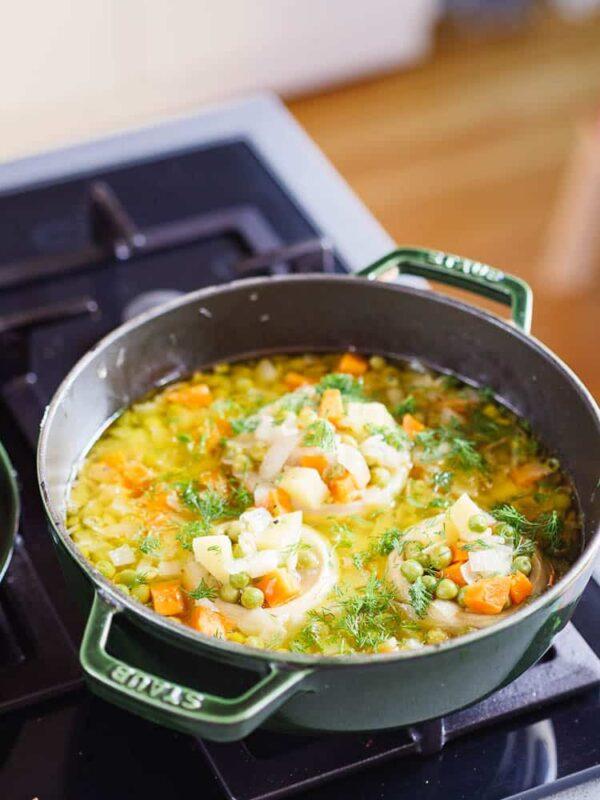 Artisjokk med erter og gulrot kokes i kasserolle, sett fra øyenivå