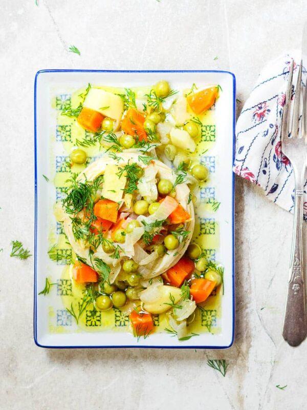 Helt artisjokkhjerte fylt med erter, gulrot, potet og olivenolje på rektangulært fat, sett ovenfra
