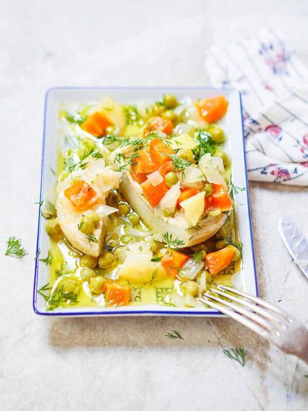 Artisjokkhjerte fylt med erter, gulrot, potet og olivenolje, delt i to, på rektangulært fat, sett fra øyenivå