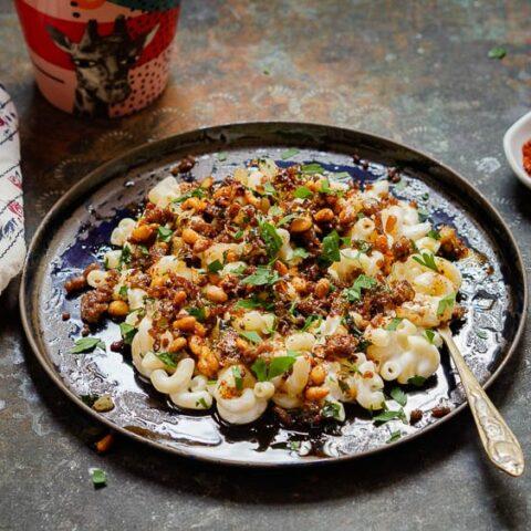 Libanesisk pasta meds yoghurtsaus og lammekjøtt på mørkeblå tallerken, sett på nært hold