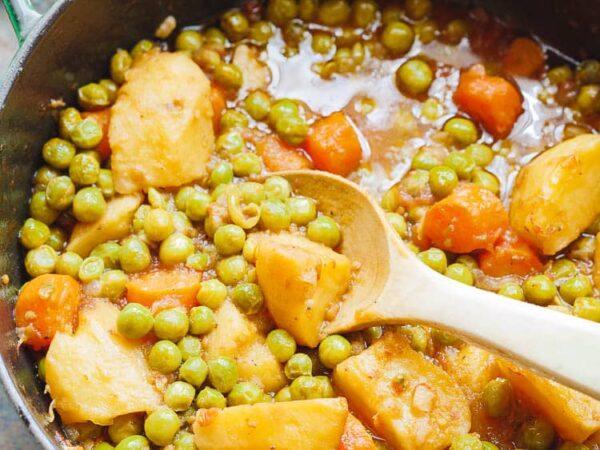 Nærbilde av erter og potet i tomatsaus i gryte