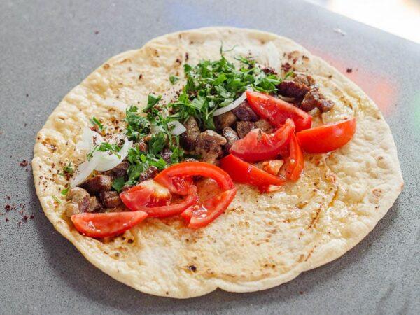 Åpent lavashbrød toppet med lammekjøtt, tomat, løk og bladpersille, sett fra siden