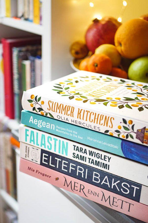 Anbefalte kokebøker liggende på kjøkkenbenk med bokhylle i bakgrunn
