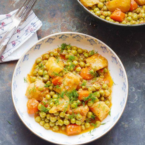 Erter og potet i tomatsaus i hvit bolle, sett ovenfra med gryte øverst til høyre