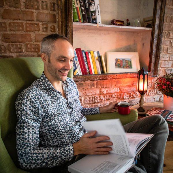 Vidar sittende i stol mens han leser i bok