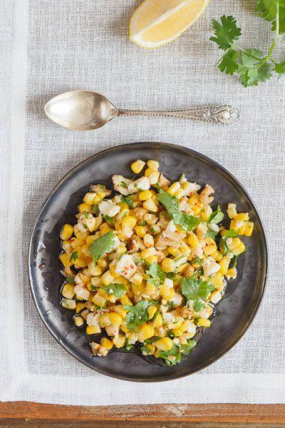Maissalat med fetaost på svart tallerken på hvit duk ovenfra og ned