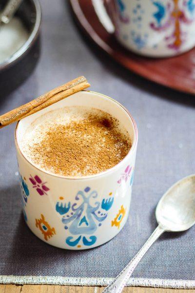 Sahlep-drikk i kopp med fargerikt mønster og kanelstang liggende på kanten, sett fra øyenivå