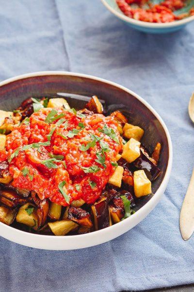 Stekt aubergine og potet med tomatsaus, sett fra øyenivå med ekstra tomatsaus i bakgrunnen