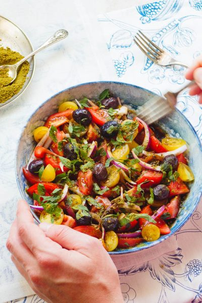 Tomatsalat med oliven og za'atar fra siden med hender som holder salatbollen