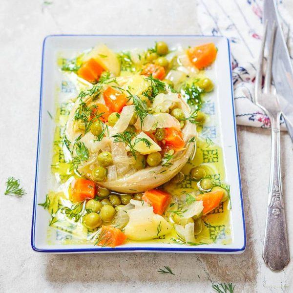 Helt artisjokkhjerte fylt med erter, gulrot, potet og olivenolje på rektangulært fat, sett fra øyenivå