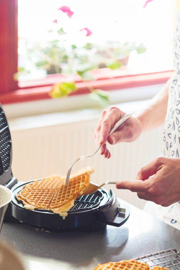 Ferdig stekt vaffel løftes av vaffeljern med gaffel og skje